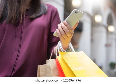 Woman look at mobile phone with paper bags in the mall while enjoying a day shopping