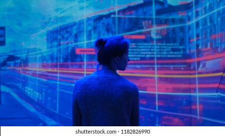 Woman looking around and watching video presentation on large display wall at futuristic technology exhibition