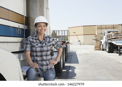 Woman looking away while standing by flatbed truck in timber yard