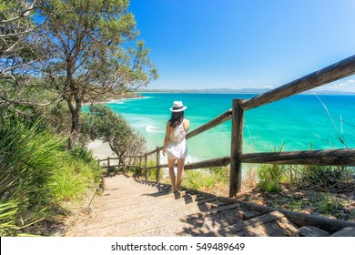 A woman looking back towards Wategoes beach at Byron Bay on Australia's east coast