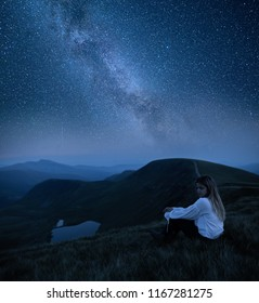 Woman looking at beautiful milky way. Beautiful woman in the mountains. Girl sitting on a rock. Milky Way at mountains. Night colorful landscape. Starry sky with hills at summer