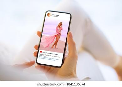 Frau auf das Foto des schönen Models auf dem Handy schauen