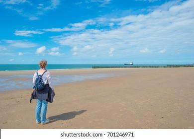 Woman looking at a boat sailing at sea along a beach