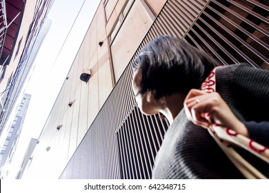 Woman looking up at buildings