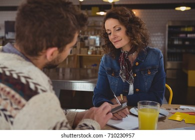 Woman looking at businessman holding digital tablet in cafe