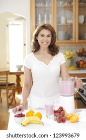 Woman looking at camera, preparing fruit smoothie, with multiple fruits on counter, in kitchen setting