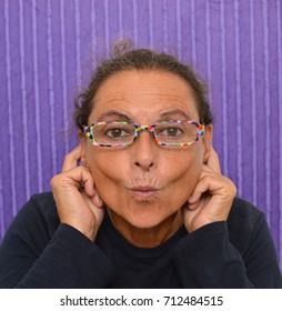 Woman looking at camera with puckered lips purple background