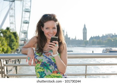 Woman looking at camera smiling, texting from bridge over River Thames, London with attractions in background