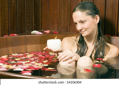 Woman looking at a candle with a neutral expression