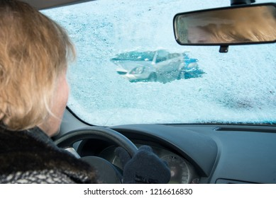 Woman is looking in a car through a small scratched gap in an icy windshield