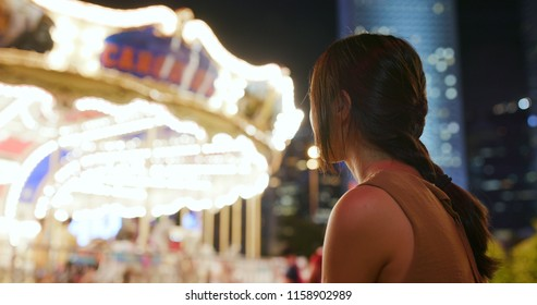 Woman looking at the carousel in the city at night
