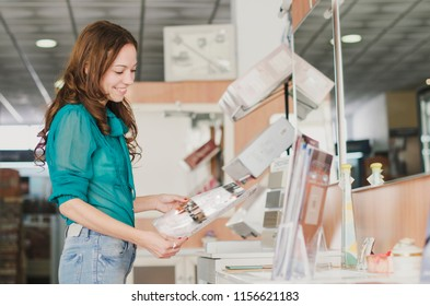 Woman looking catalog in bath store for choosing baths and water, faucet, washbasin, ceramic, tiles…