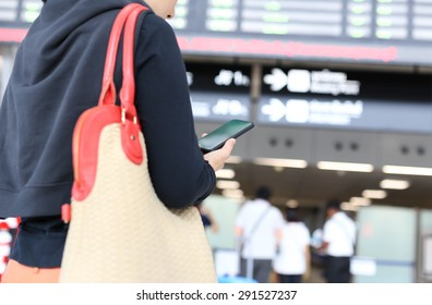 Woman looking and checking her flight time on smart phone mobile in the airport terminal