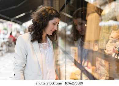 Woman looking chothes store showcase
