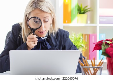 Woman looking at computer screen through a magnifying glass