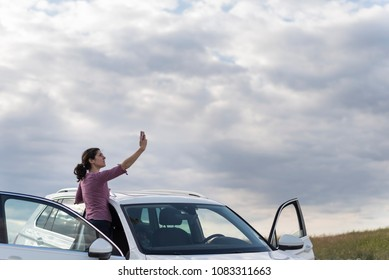 woman looking for coverage for the mobile phone in her suv car