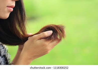 Woman looking at damaged splitting ends of hair on nature background, Haircare concept