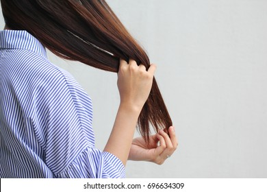 Woman looking at damaged splitting ends of hair, Haircare concept