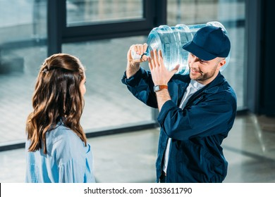 Woman looking at delivery man holding water bottle