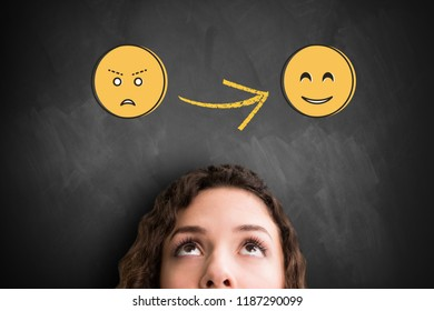 woman looking up to a emoticon with bad mood that changes to a happy emoticon