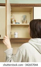 Woman Looking In Empty Food Cupboards