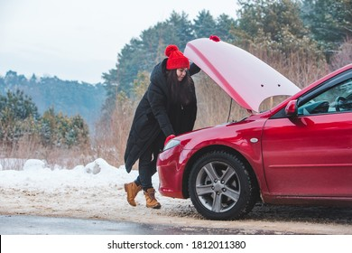 woman looking at engine broken car at winter road side