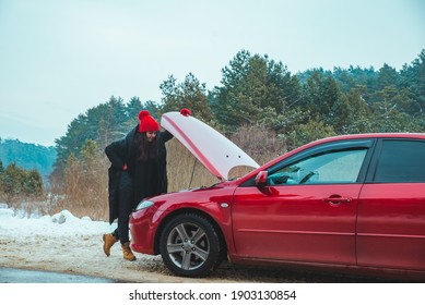 woman looking at engine broken car at winter road side copy space