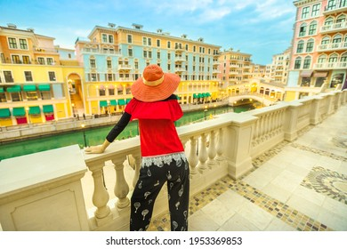 Woman looking famous bridge in Venice Doha city. Caucasian tourist at Qanat Quartier in the Pearl-Qatar, Persian Gulf, Middle East. Aerial view of luxurious and picturesque residential district.