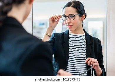 Woman looking with glasses in mirror at optician store
