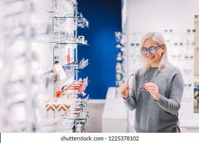 Woman looking at glasses at optic store. Shopping, choosing eyewear. Vision defect.