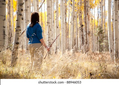 Woman Looking At Golden Autumn Leaves Through Forest of Aspen Trees