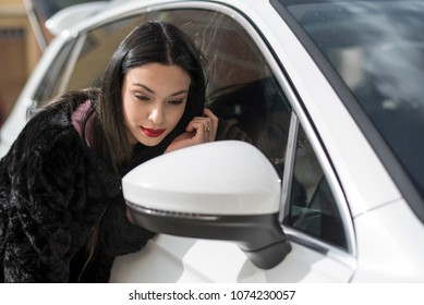 Woman looking her beauty face in suv white car mirror