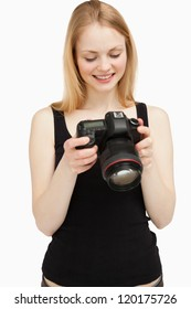 woman looking at her camera wile smiling against white background