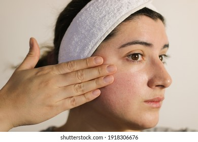 Woman looking at her face. A person with sensitive skin and rosacea.