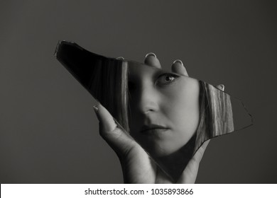 Woman looking at her face in a shard of an broken mirror artistic conversion