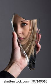 Woman looking at her face in a shard of broken mirror