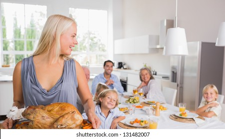 Woman looking her family and holding a turkey