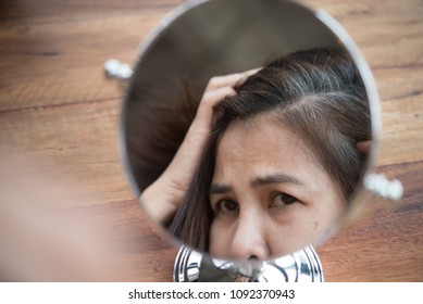 woman looking at her hair for gray hair problem