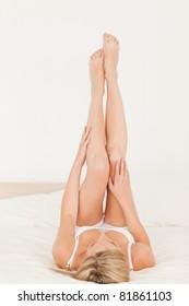 Woman looking at her legs in her bedroom