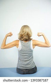 Woman looking at her muscles.