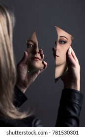 Woman looking at her  own face in two shards of broken mirror