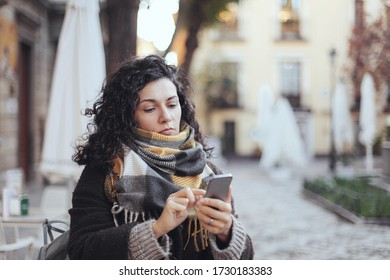 A woman looking at her phone. Small European town, empty street, old buildings