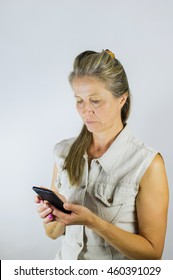 Woman looking at her phone with a very serious and concerned expression.