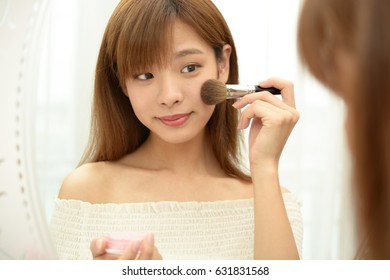 Woman looking at her reflection in a mirror and applying makeup on herself.