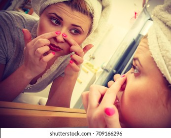 Woman looking at her reflection in mirror thinking about her complexes having serious face expression, analyzing face skin complexion squeezing pimples