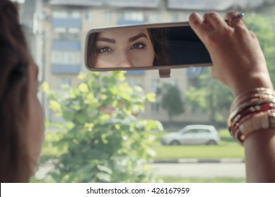 Woman looking at her reflection in the rearview mirror of car. Concept: beauty, fashion, transportation