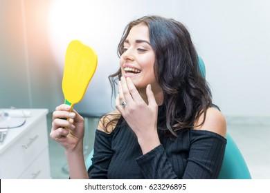 Frauen, die ihre Zähne anschauen. Lächelnde Dame im Zahnarztbüro. Lächle als Meisterwerk.