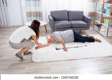 Woman Looking At Her Unconscious Father Lying On Carpet