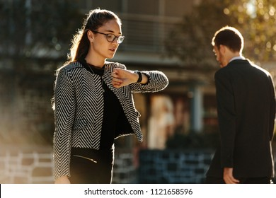 Woman looking at her wrist watch while commuting to office in the morning. Woman going to office checking time while walking on street with sun flare in the background.