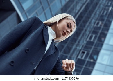 Woman looking at her wrist watch while going to office checking time on the city background